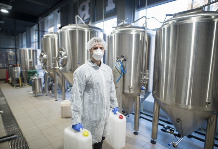 Industrial worker technologist in white protective suit with hairnet and mask holding plastic cans with chemicals in food factory production line.