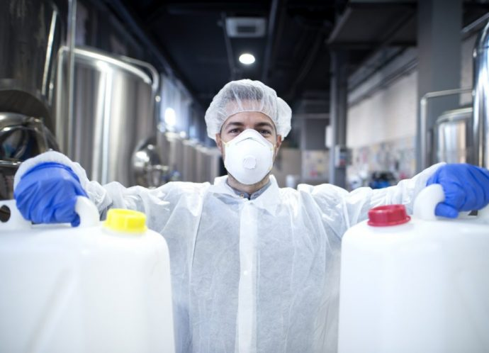 Industrial worker with protective mask and white uniform holding plastic cans for chemical industry.